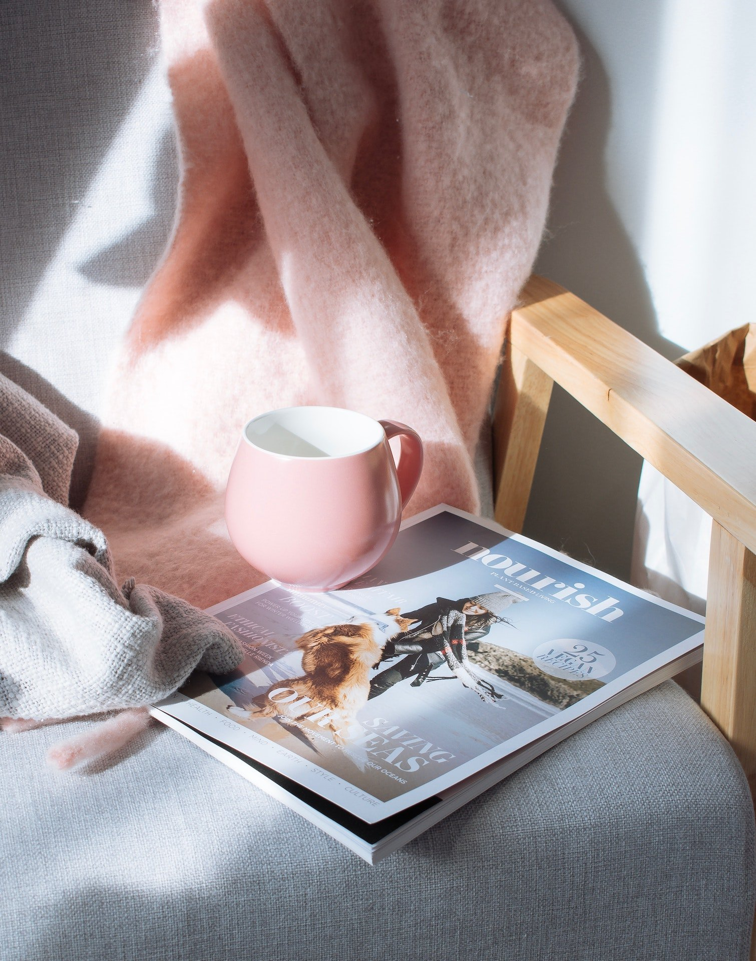 Pink mug and magazine on chair with pink blanket.
